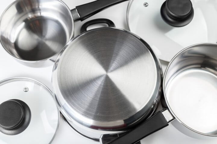 Stainless steel pots and pans on white background