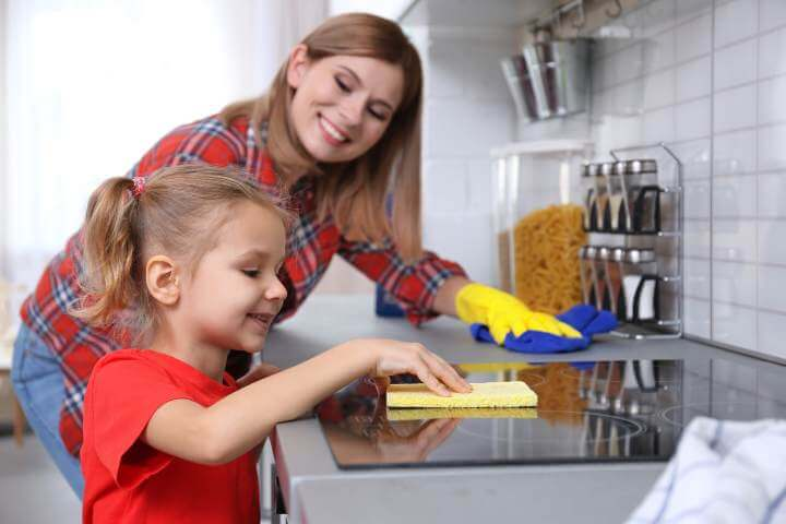 girl cleaning cooktop with sponge