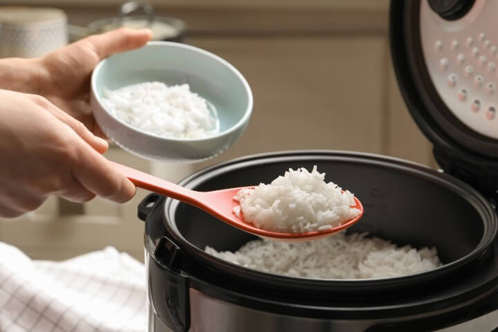 scooping rice from rice cooker