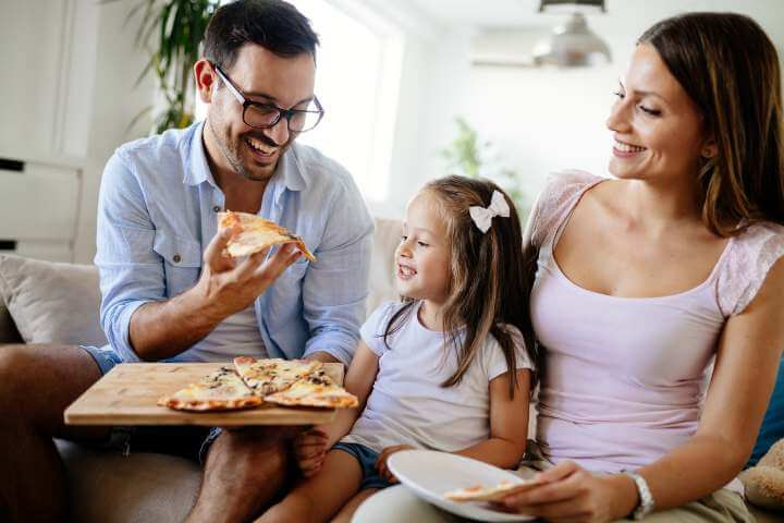 father holding a slice of pizza