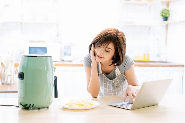 woman using air fryer on the table